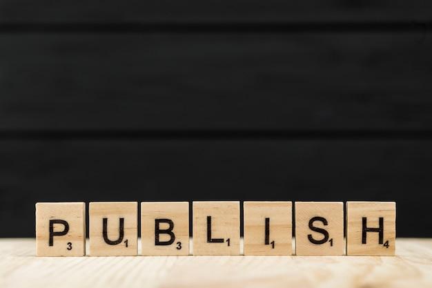 La palabra publicar deletreada con letras de madera.