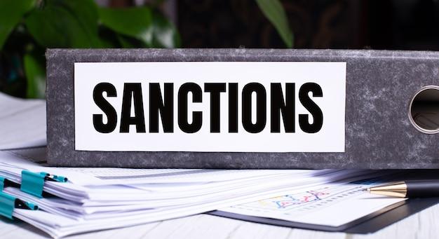 La palabra sanciones está escrita en una carpeta de archivo gris junto a los documentos.