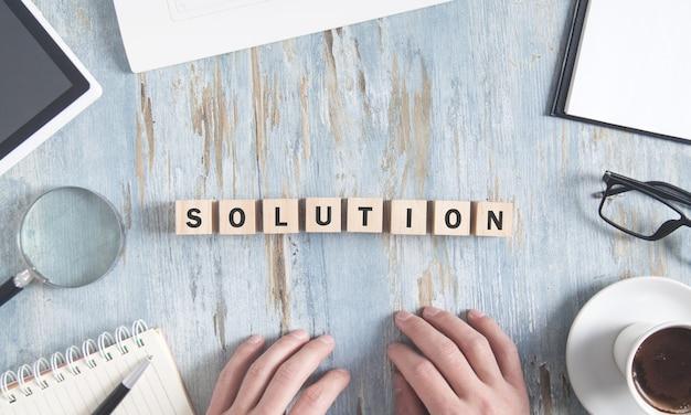 Palabra de solución en cubos de madera con objetos de negocio y manos humanas