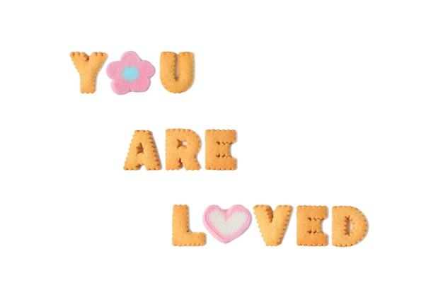 La palabra te aman deletreada con galletas del alfabeto y dulces de malvavisco