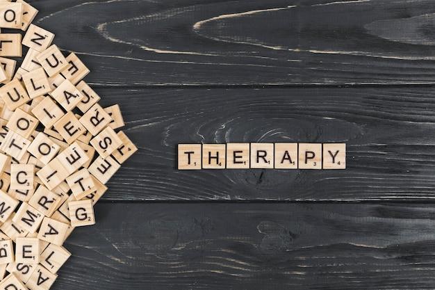 Palabra de la terapia en el fondo de madera