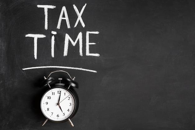 Palabra del tiempo del impuesto escrita sobre el reloj de alarma en la pizarra