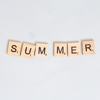 Palabra de verano escrita en bloque de madera sobre superficie gris