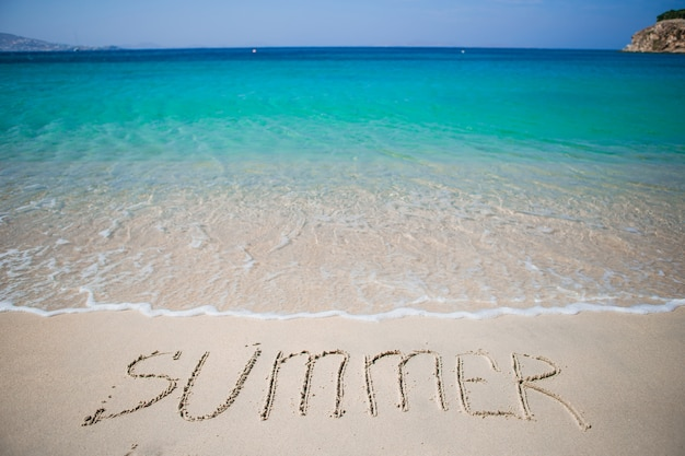 Palabra de verano escrita a mano en la playa de arena con suave ola oceánica en el fondo