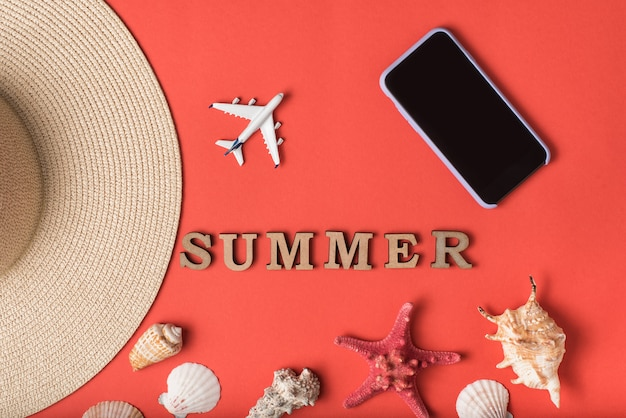 Palabra de verano de letras de madera. conchas marinas, parte de un sombrero, avioneta y teléfono inteligente, live coral wall. endecha plana. concepto de viaje