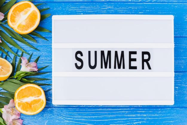 Palabra del verano en la tableta cerca de las hojas de la planta con naranjas frescas