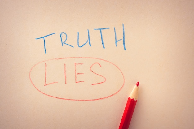 Palabra de verdad y una mentira subrayada, escrita en lápices de colores sobre papel.
