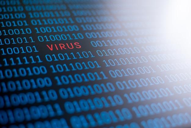 La palabra virus, escrita en letras rojas sobre un código binario con luz azul blanca en la parte superior derecha