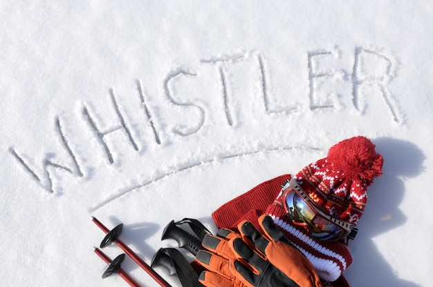 La palabra whistler escrita en la nieve con bastones de esquí, gafas y sombreros.