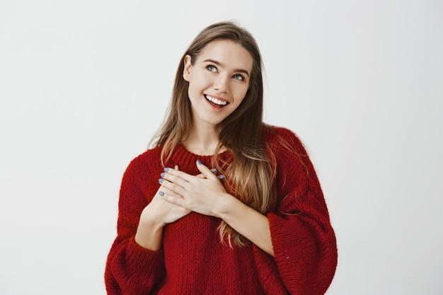 Las palabras acertaron en el corazón. soñadora novia hermosa en suéter rojo suelto, cogidos de la mano en el pecho y mirando con expresión romántica complacida, sonriendo ampliamente mientras imagina cosas positivas