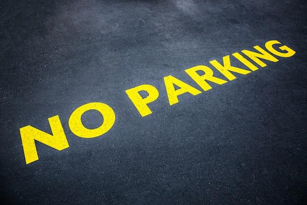 Palabras amarillas sin estacionamiento pintadas en la carretera de asfalto