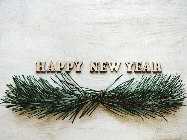 Palabras año nuevo en una pizarra con rama de árbol