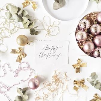 Palabras de caligrafía feliz navidad y marco de decoración navideña con bolas de navidad, oropel, arco, eucalipto.