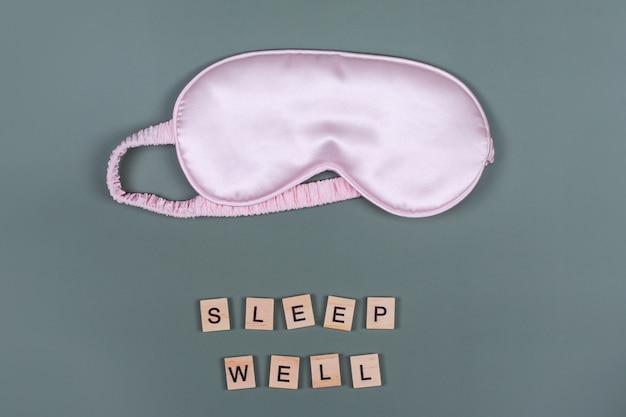 Palabras dormir bien y antifaz rosa para dormir, vista superior, buenas noches, concepto de vuelo y viaje
