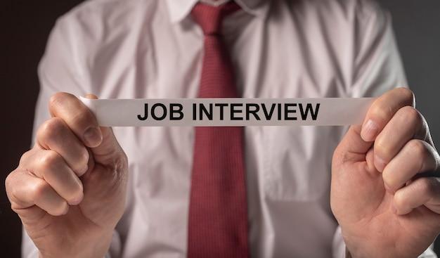 Palabras de la entrevista de trabajo en papel en manos del empleador, concepto de carrera.