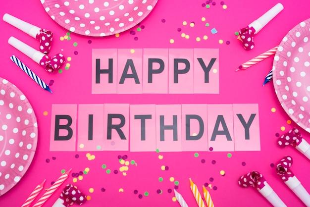 Palabras de feliz cumpleaños con platos y silbatos y velas.