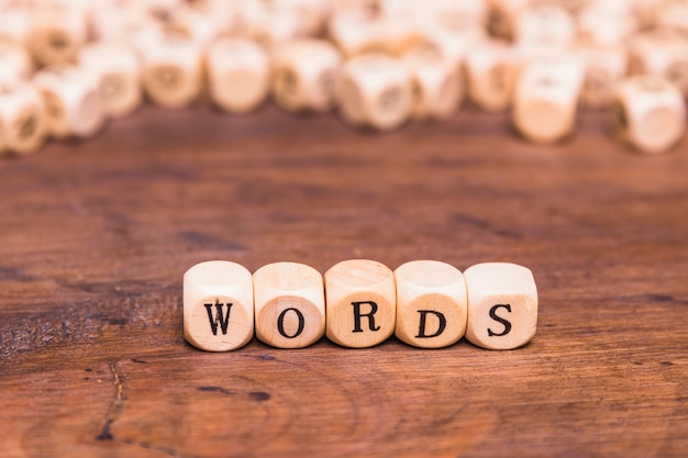 Palabras letra hecha con cubos de madera sobre escritorio marrón
