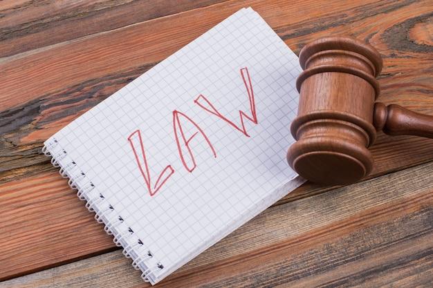 Palabras de leyes de primer plano escritas en el bloc de notas en espiral y martillo