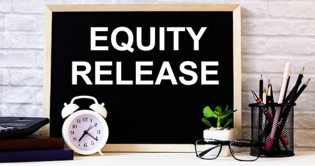 Las palabras liberación de equidad están escritas en la pizarra junto al reloj despertador blanco, vasos, planta en maceta y lápices en un soporte.