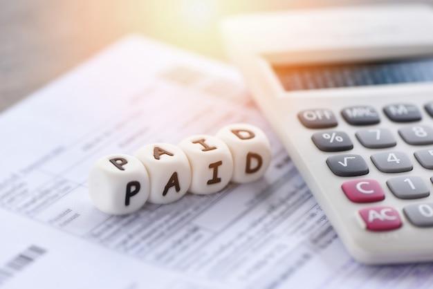 Palabras pagadas y calculadora en papel factura de factura