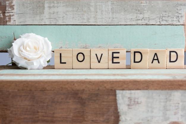Palabras del papá del amor con la rosa blanca en la tabla rústica del vintage