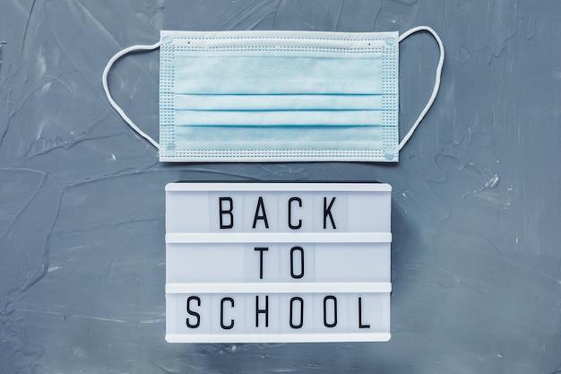 Palabras de regreso a la escuela y máscara médica desechable sobre fondo gris.