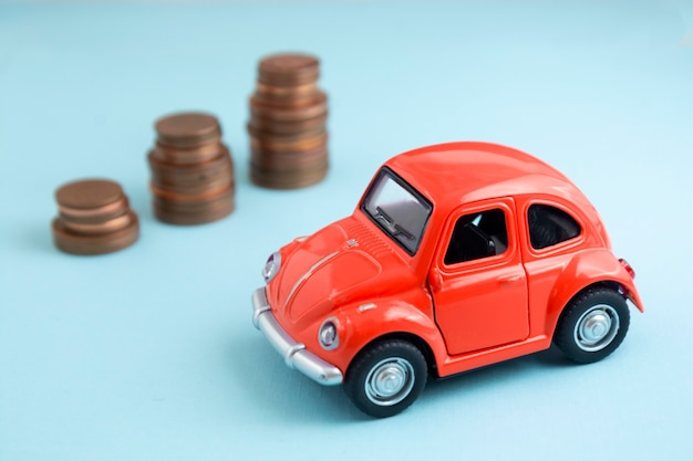 Palabras de seguro de automóvil, modelo de automóvil rojo y monedas sobre fondo azul.