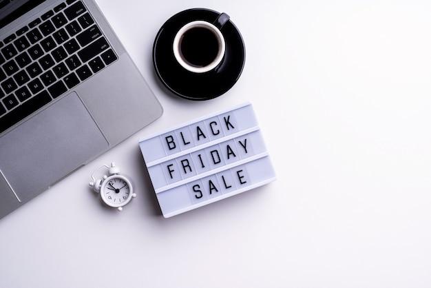 Palabras de venta de viernes negro en caja de luz con taza de café, computadora portátil y reloj
