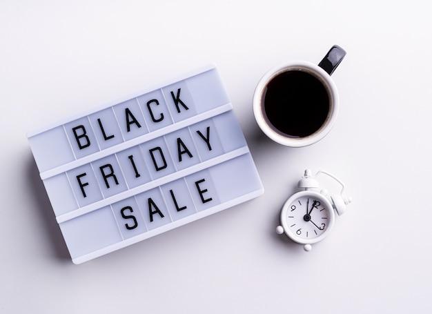 Palabras de venta de viernes negro en caja de luz con taza de café y reloj