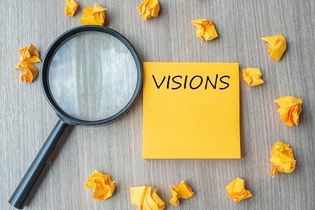 Palabras de la visión en nota amarilla con papel desmenuzado y lupa.