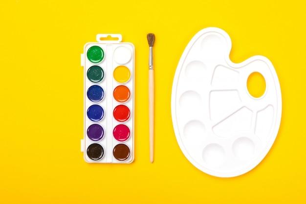 Paleta de arte plástico con pinturas de acuarela y pincel sobre fondo naranja