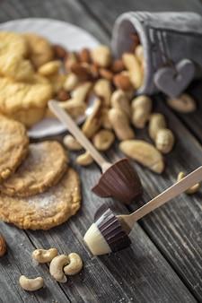 Paleta de chocolate en forma de una taza pequeña y varias nueces en un cubo de madera