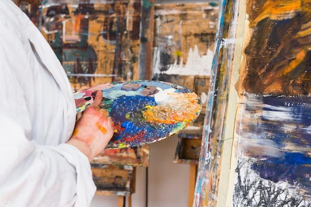 Paleta de colores desordenados en la mano de la mujer en el taller