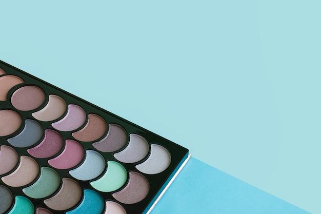 Paleta de colores de maquillaje sobre fondo azul.