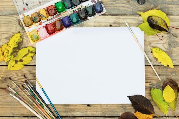 Paleta de pintura plástica con pintura, pinceles y hojas amarillas en la mesa de madera