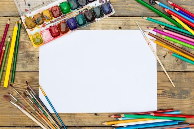 Paleta de pintura plástica con pintura y pinceles sobre mesa de madera