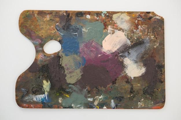 Paleta de pintura con varios colores sobre fondo blanco.