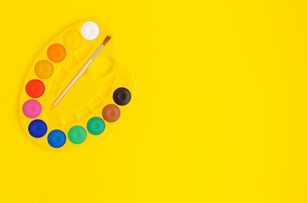 Paleta de pinturas de acuarelas sobre fondo amarillo. copia espacio, vista superior.