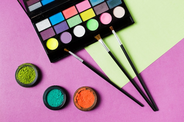 Paleta de sombras de ojos de colores y pinceles cosméticos.