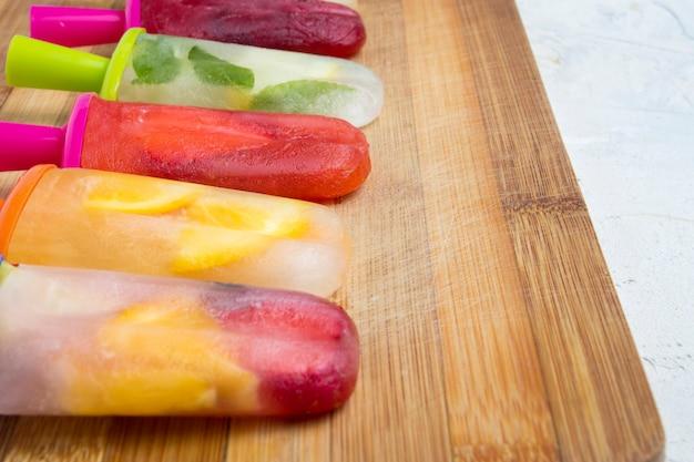 Paletas frutales coloridas caseras en una tabla de madera y contra.