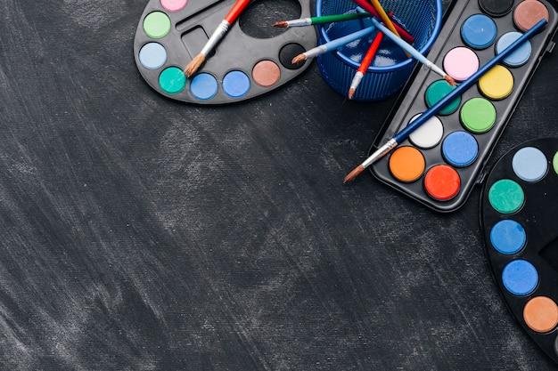 Paletas multicolores de pinturas sobre fondo gris.