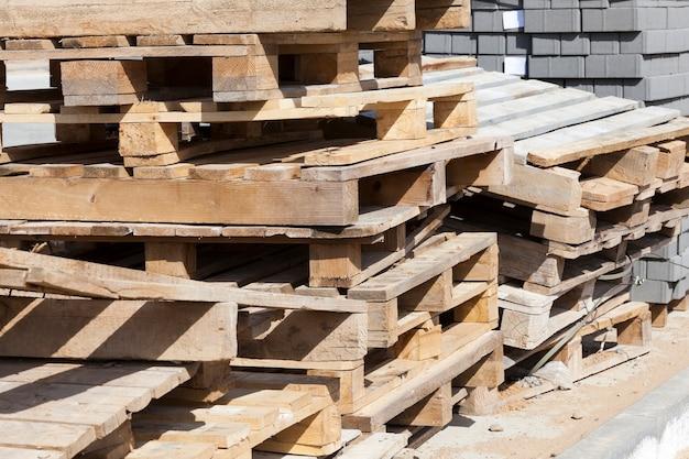 Palets de madera vacíos y tejas de obra nueva para la colocación de caminos y carreteras