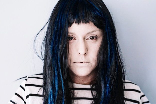 Pálida niña con el pelo azul mirando la cámara