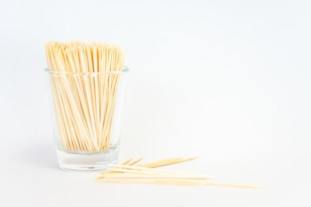 Palillo de dientes aislado, palillo de bambú en un vaso sobre fondo blanco