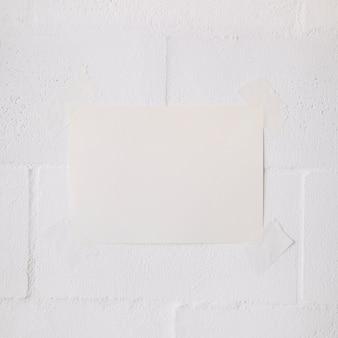 Palillo de papel en blanco blanco con cinta sobre fondo de pared blanca