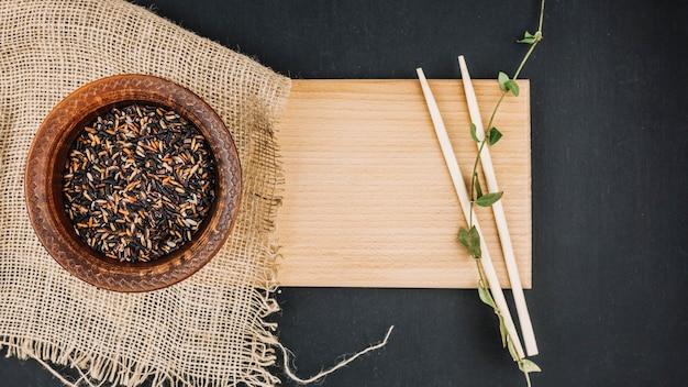 Palillos y arroz negro en el tablero de madera