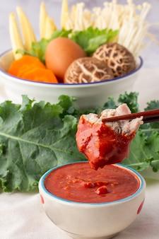 Palillos de cerdo recogidos sumergidos en un tazón de salsa sukiyaki. muchas verduras en un tazón blanco incluyen zanahorias, maíz baby, hongos shiitake, agujas doradas, apio y huevos de gallina.