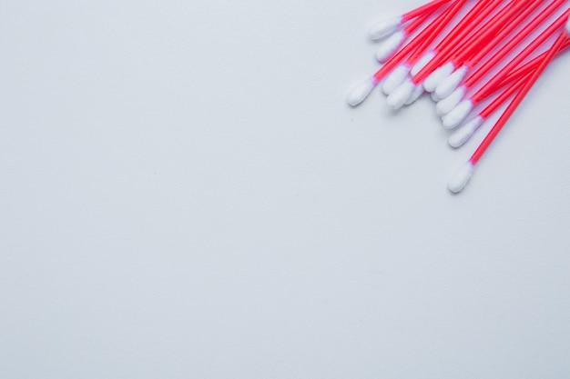 Los palillos desechables para los oídos con una varita roja yacen sobre un fondo blanco en la vista superior de la esquina superior ...