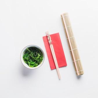 Palillos entre ensalada de servilletas de bambú y algas marinas