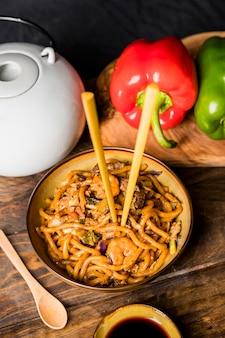 Palillos insertados en fideos udon con camarones en mesa de madera